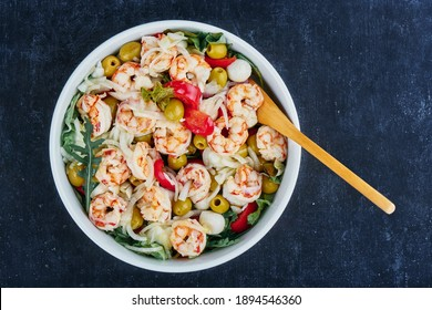 Salad from shrimp, olives, mozzarella, tomatoes and olive oil sauce, close up, top view