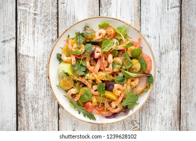 salad with shrimps and assorted salads (arugula, cherry tomatoes, chard, spinach) on white wooden background