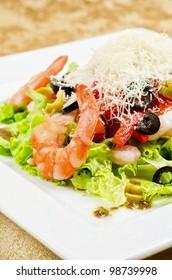 Salad with shrimps, caviar, calamaries, lettuce, olive, tomato and mozzarella