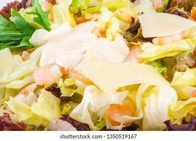 Salad with shrimps, greens mix and parmesan cheese on white plate. Close up