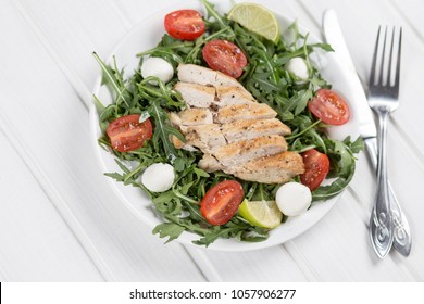 salad with sliced chiken meat, rocket leaves, cherry tomatoes, mozzarella, eggs, served in white round plate