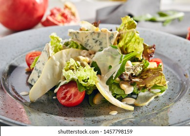 Salad with sliced pears, gorgonzola cheese, greens and pine nuts close up. Fruit salat with Italian blue cheese, tomatoes, green lettuce leaves, thin slices of pear and white sauce