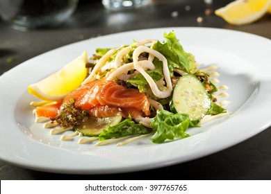 Salad with Sliced Salmon and Cucumbers. Garnished with Lemon Slice