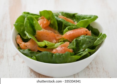 salad with smoked fish on white bowl