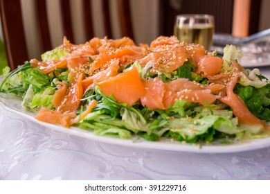 A salad of smoked salmon and lettuce, arugula, dill dressed with sauce and dusted with sesame seeds on a white plate, blurred background. Salmon salad ready to eat. Horizontal. Daylight. Close.
