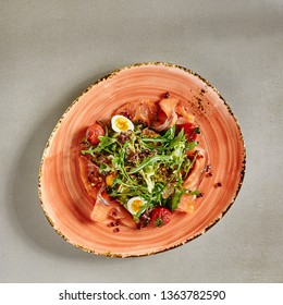 Salad with Smoked Salmon, Red Caviar, Whole Dried Cherry Tomatoes, Quail Eggs and Greens. Seafood Dish with Fresh Lettuce Leaves and Arugula Beautifully Laid on Ceramic Plate Top View