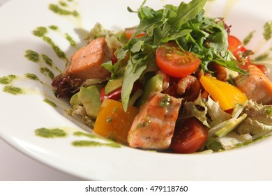 Salad with smoked salmon and vegetables and Arugula on plate