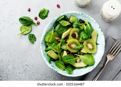 Salad of spinach baby leaves, watercress, kiwi, avocado and pomegranate in old ceramic plate on gray concrete background. Selective focus. Top view. Copy space.
