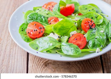 salad with spinach, cherry tomatoes, cheese and a dressing of lemon, honey and olive oil. close-up