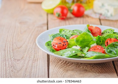 salad with spinach, cherry tomatoes, cheese and a dressing of lemon, honey and olive oil. copy space