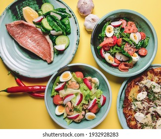 Salad with spinach, eggs and radish in a bowl over bright yellow background. Fish fillet steak, potato and cheese pizza. Full table flat lay. Healthy eating concept.