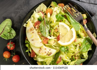 Salad. Spring vegetable salad. Fresh vegetable salad with tomatoes, apple, nuts, seeds and lemon. Olive oil pouring into bowl of salad.