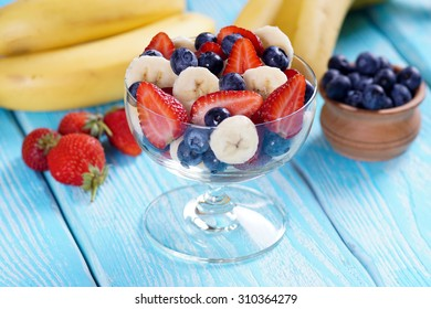 Salad strawberry banana and blueberries on blue board.