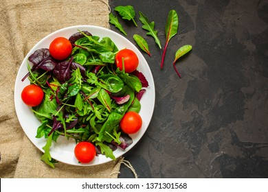 salad with tomato, lettuce, arugula, spinach and other leaves. food background. top