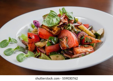 salad with tomato, zucchini and balsamic sauce, onions and herbs. decorated with micro greens sunflower
