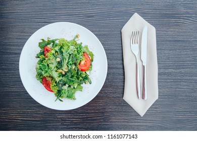 Salad with tomatoes, arugula, sunflower seeds and herbs on white ceramic plate over rustic wood background. Summer salad with tomatoes, arugula