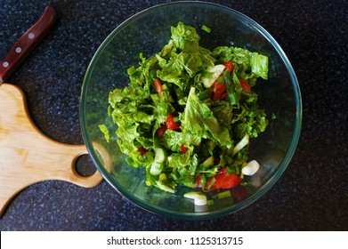 Salad with tomatoes, cucumbers, lettuce and green onions. Dark stone background. View from above.