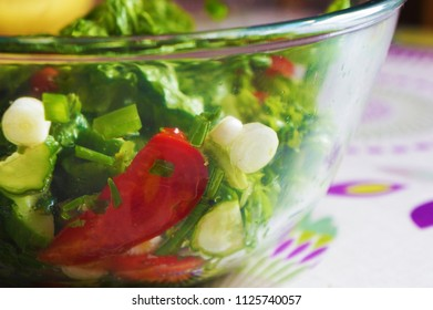 Salad with tomatoes, cucumbers, lettuce and green onions in bowl. Closeup side view.