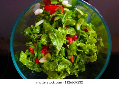 Salad with tomatoes, cucumbers, lettuce and green onions. View from above.