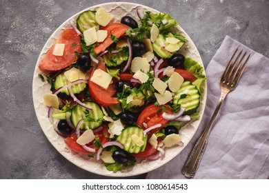 Salad with tomatoes, cucumbers, olives, red onion and parmesan cheese.