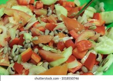 Salad with tomatoes, cucumbers, peppers, pumpkin seeds, sunflower seeds, celery and beans tiger's eye. Vegan Food.