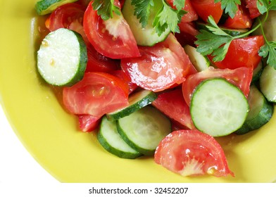 Salad of tomatoes and cucumbers in yellow plate on white background.