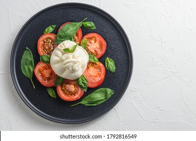 Salad with traditional italian burrata cheese made from cream and milk of buffalo or cow on black flat plate top view flatlay white concrete background space for text - Shutterstock ID 1792816549