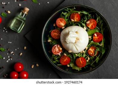 Salad with traditional italian burrata cheese with arugula and tomatoes om dark concrete table with with cooking ingredients cherry tomatoes, basil, garlic and olive oil. Top view.  - Shutterstock ID 1927460174