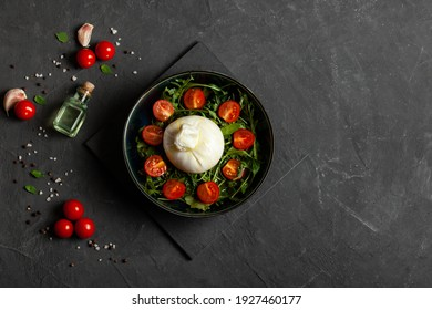 Salad with traditional italian burrata cheese with arugula and tomatoes om dark concrete table with with cooking ingredients cherry tomatoes, basil, garlic and olive oil. Top view. Copy space.  - Shutterstock ID 1927460177