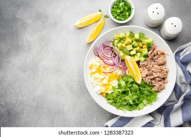Salad with tuna, avocado, onion, egg and lemon. Spring healthy delicious lunch on light grey background