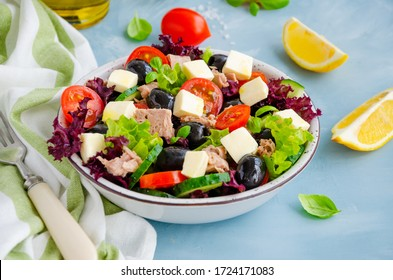 Salad with tuna, fresh vegetables, olives and feta cheese in a bowl on a light blue concrete background. Healthy food. Horizontal orientation