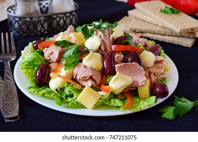 Salad with tuna, olives, cheese, paprika, lettuce and mayonnaise.