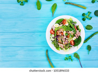 Salad with tuna, tomatoes, quail eggs, asparagus and onions on wooden background