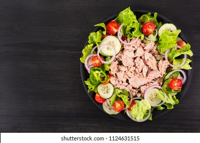 Salad with tuna and vegetables. Mediterranean food. Top view. Copy space.