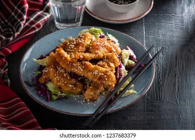 Salad with warm glazing chicken, sprinkled with sesame seeds. Chinese cuisine. Asian culture.
