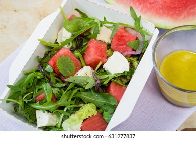 Salad with a water-melon, cheese feta, a radish and black sesame in a kraft boxes.
