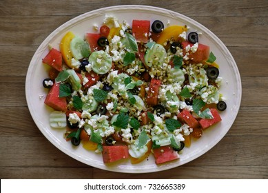 Salad from watermelon, tomato, cucumber, olives, pine nuts, on an oval plate seen from above on a wood background