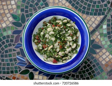 Salad with white beans and herbs on a plate with blue and green rim seen from above on a table with a mosaic pattern