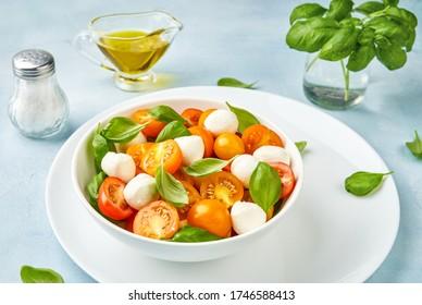 Salad with yellow tomato cherry and mini mozzarella cheese in white bowl on white plate. Bocconcini mozzarella cheese with fresh basil leaves in caprese salad.