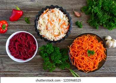Salads from fresh vegetables: cabbage, carrots, beets. Korean spicy salads in bowls on a wooden table. Top view. Vitamin menu. Vegan cuisine.