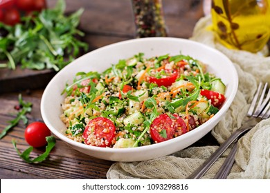 Salads with quinoa,  arugula, radish, tomatoes and cucumber in bowl on  wooden background.  Healthy food, diet, detox and vegetarian concept.