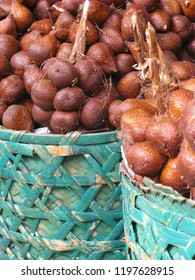The salak fruit also called snake fruit of the salak palm tree at an Asian market in blue baskets, Bali Indonesia
