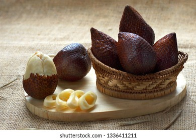 Salak fruit known as snake fruit native from Java island on bamboo basket  served on the table