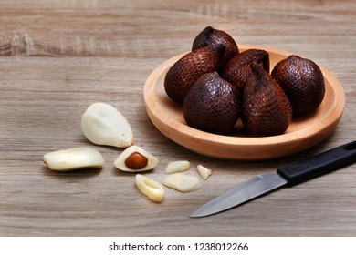 Salak fruit ( Salacca zalacca) and a knife  on wood texture background