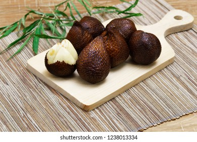 Salak fruit ( Salacca zalacca) on cutting board and leaves on wood texture background