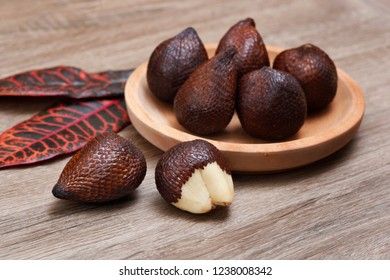 Salak fruit ( Salacca zalacca) in wooden plate on wood texture background