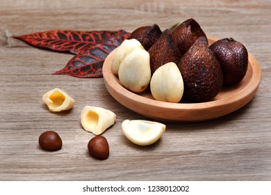 Salak fruit ( Salacca zalacca) in a wooden plate on wood texture background