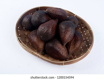 Salak group of fruit in bamboo tray on white background. Salak is a species of palm tree native to Java and Sumatra in Indonesia.