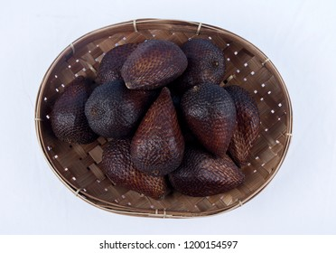 Salak group of fruit in bamboo tray on white background. Salak is a species of palm tree native to Java and Sumatra in Indonesia. Flat lay.