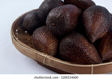 Salak group of fruit in bamboo tray on white background. Salak is a species of palm tree native to Java and Sumatra in Indonesia. Close up.
